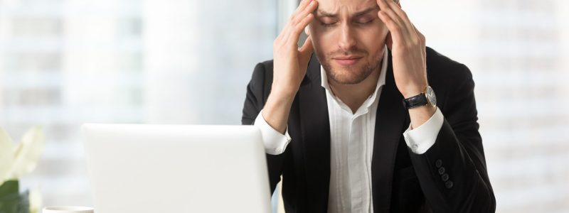 Frustrated man squeezes temples with hands at desk in front of laptop. Tired businessman suffers from headache at workplace. Entrepreneur feels chronic fatigue, work stress because of business problem